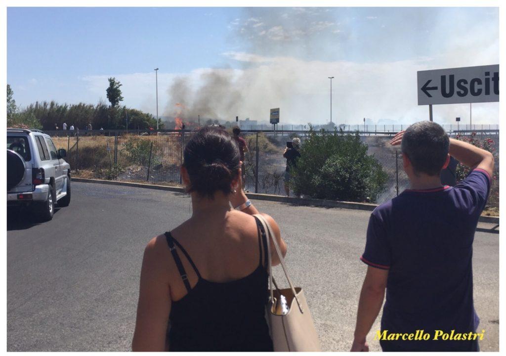 Persone osservano le fiamme nei parcheggi della città mercato